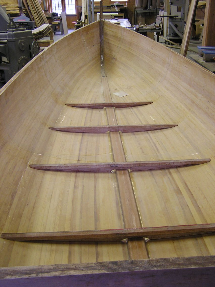 This is a cold molded, cedar stip and glass, vacuum bagged hull that was built at the school and had been sitting for a couple years and not getting much attention – so Andy bought it for himself. He's in the process of adding floors and interior structure. Eventually, it will have a cuddy cabin and be powered by a 15 – 25 hp outboard engine. Perfect for toolin' around Les Cheneaux.