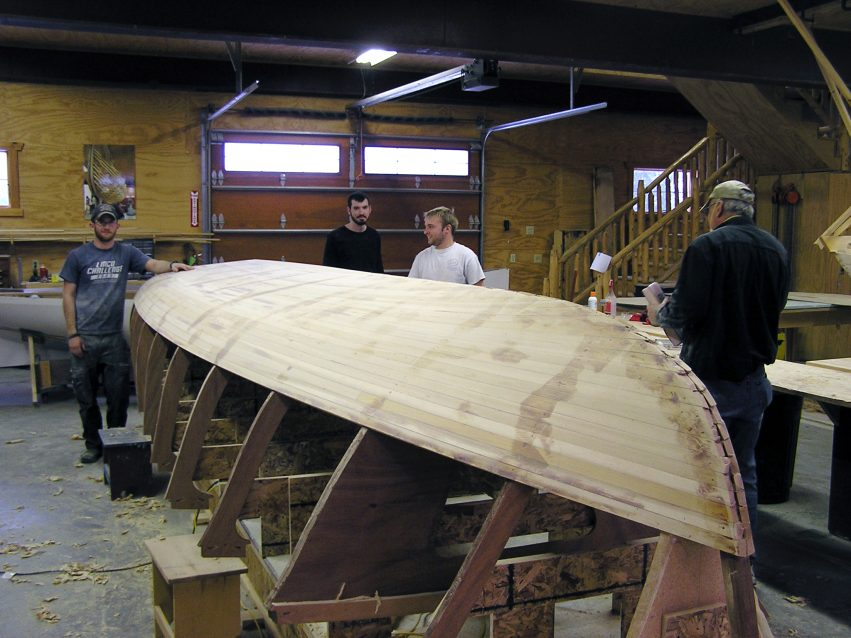 The cedar on and getting sanded fair before getting coated with epoxy and glassed by second year students: (l-r) Troy Huesdash, Matt Edmondson, Kris Kindt and Del Jacobs.